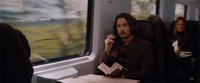 列車に乗り電子タバコを吸うフランク(ジョニー・デップ)