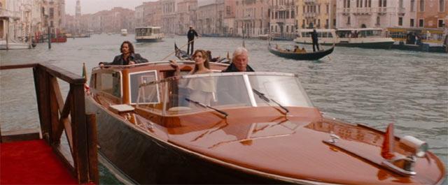 ベネチアでお洒落なボートに乗るエリーズとフランク