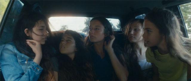 5人一緒に車の後部座席に座っているシーン