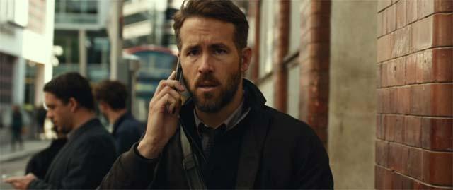 困った表情で携帯電話を持つビル・ポープ(ライアン・レイノルズ)