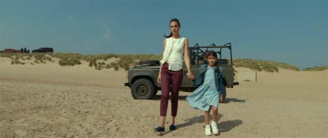 砂浜を歩くジル・ポープと娘