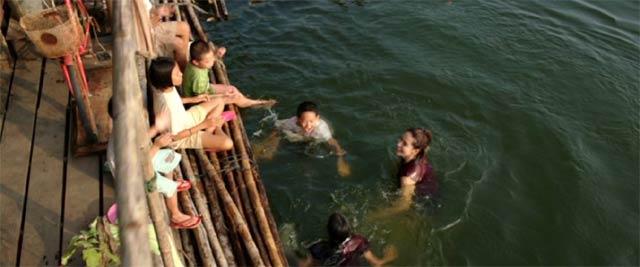学校の前で泳ぐエーン先生と子供達