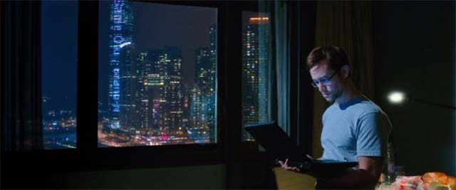 夜ホテルで夜景をバックにノートPCを見るスノーデン
