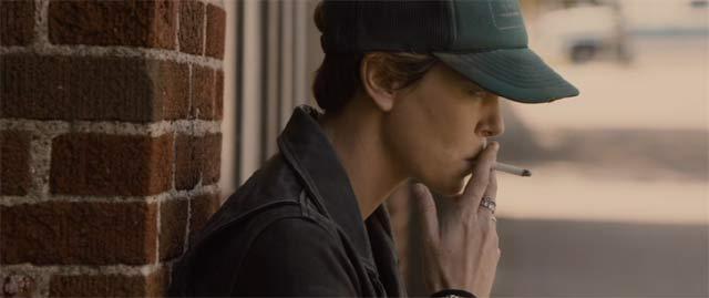 キャップを被り、タバコを吸うシャーリーズ・セロン